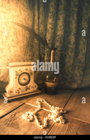 romantic still life with a vintage clock, glass bottle, feather and pearls - Stock-Bilder