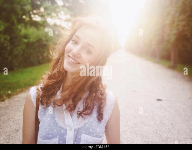 Portrait Of A Smiling Young Woman On Country Road - Stock Image