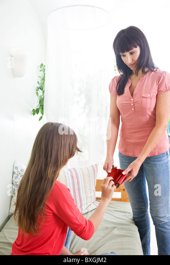 Mother showing empty wallet to her teenaged daughter - Stock Image