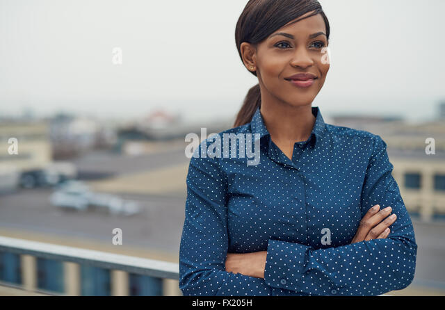 Confident friendly black business woman standing with folded arms on the rooftop of an urban commercial building - Stock Image