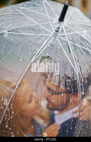 Romantic valentines standing under umbrella in the rain - Stock-Bilder