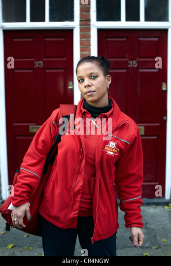 The Great British Postman. Postal worker on the streets of UK. Female postal worker - Stock Image