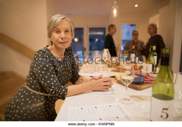 Portrait confident senior woman rating white wine at wine tasting party - Stock Image