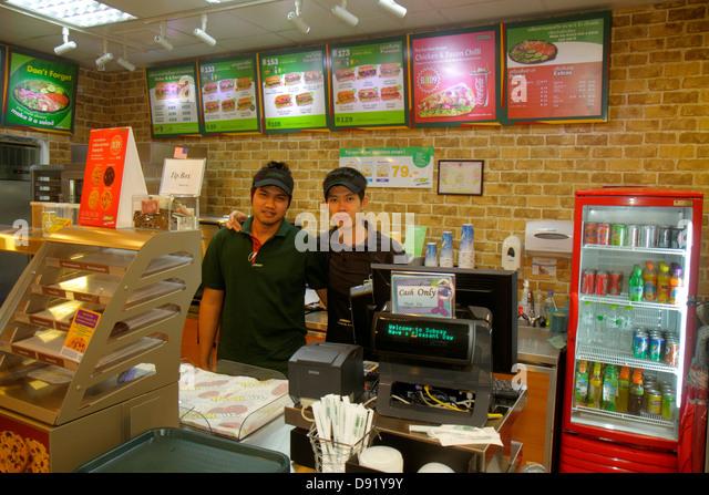 Bangkok Thailand Pathum Wan Rama 1 Road Subway subs sandwich shop restaurant counter Asian man employee cash only - Stock Image