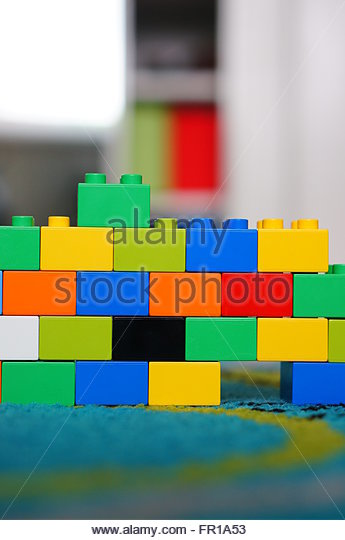 Stacked colorful plastic Lego Duplo blocks on carpet - Stock Image