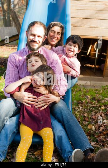 Family in a row between each others legs on playground slide, looking at camera smiling - Stock Image