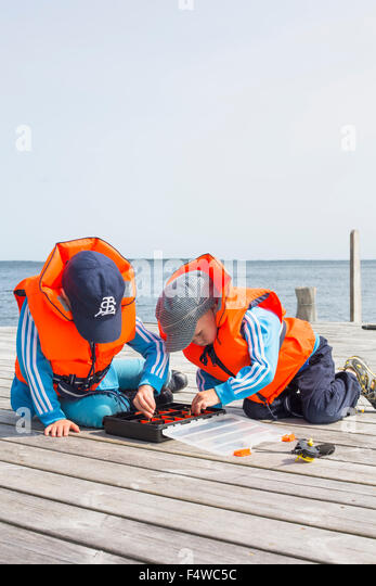 Boys (4-5, 6-7) playing with fishing equipment on jetty - Stock Image