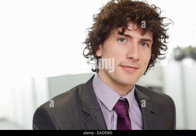 Portrait of businessman with curly hair wearing suit and tie - Stock Image