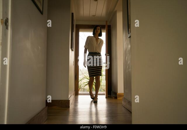 Mid adult woman arriving in house hallway - Stock Image
