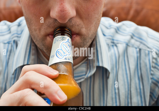 Young professional man drinking non-alcoholic beer/lager - Stock Image