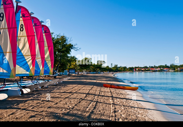 Line of catamaran sailboats with colorful sails early morning on Negril beach and kayak at the water - Stock Image