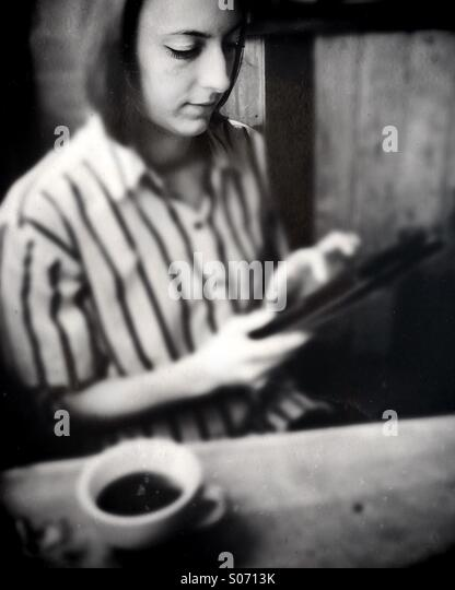 A young woman using a tablet computer - Stock Image