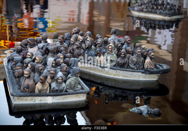 Dismaland, Bemusement Park,  'Boating pond' by Banksy, featuring boats loaded with sculptures of migrants - Stock Image