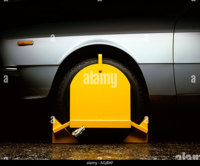 Yellow Wheel Clamp on a silver car - Stock Image