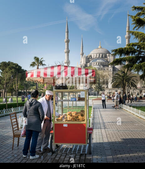 Istanbul, Turkey - April 16, 2017: Tourist buying fast food meal from a traditional Turkish Simit (Bagel) cart in - Stock Image
