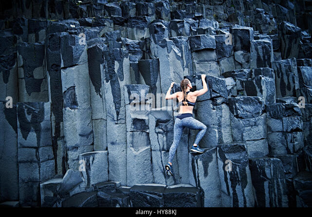 Happy confident young women climbing on basalt rock in southern Iceland - Stock Image