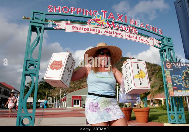 Sint Maarten Philipsburg Dutch White women duty free rum liquor straw hats cruise dock entrance - Stock Image