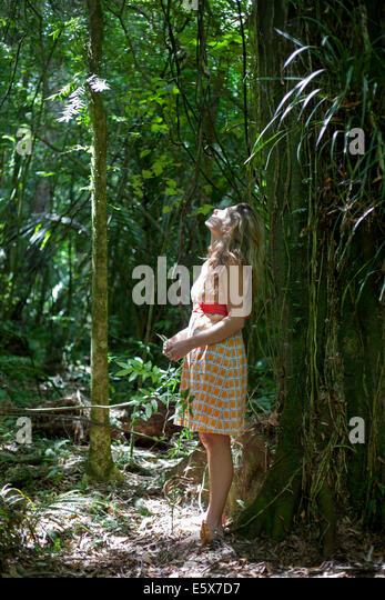Mid adult woman leaning against tree in jungle gazing upward - Stock-Bilder