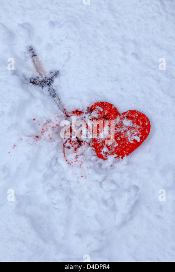 a snow-covered heart with a dagger and blood - Stock-Bilder
