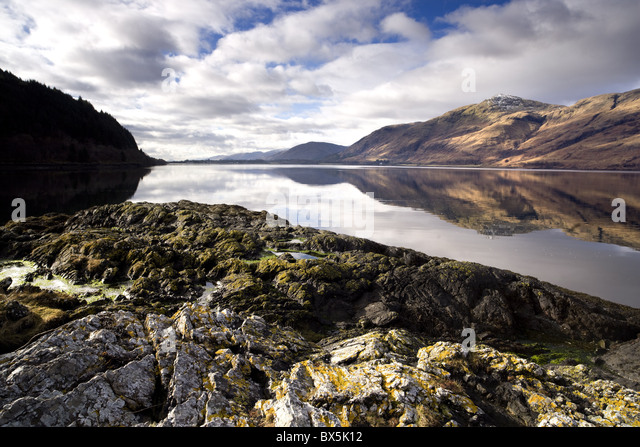 Winter view of Loch Linnhe in calm weather with reflections of distant mountains and rocky foreshore, Highland, - Stock Image
