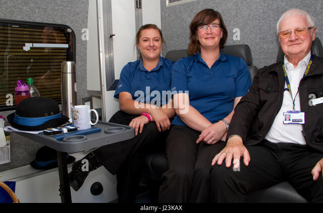 Two women PCSOs and a male police volunteer take a break in a mobile police station - Stock Image