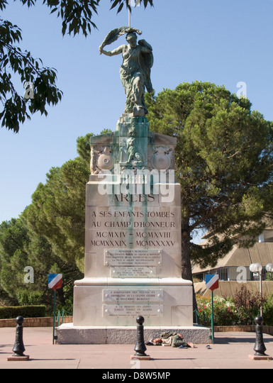 War memorial with a man asleep on the pavement at the bottom, Arles, France - Stock Image