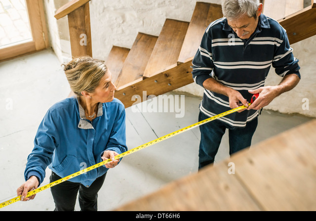 Senior couple doing DIY, using measuring tape - Stock Image