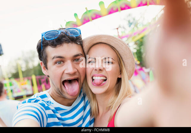 Happy couple at fun fair taking selfie   tongues out - Stock Image