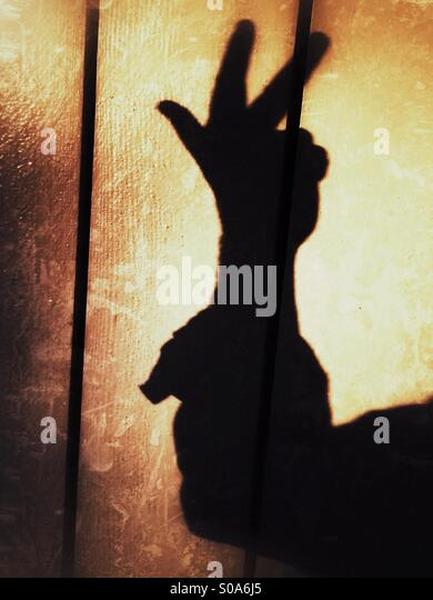 A man casting a shadow on a wall, counting on his hand. Number three. - Stock Image
