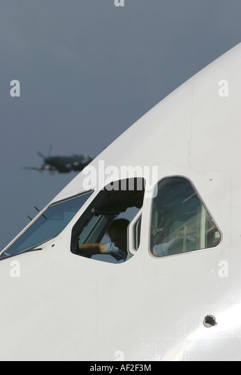 Pilot of largest passenger airplane Airbus A380 preparing for departure and II WW Spitfire flying in the background - Stock Image