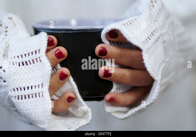Woman with painted nails holding bowl in hand - Stock Image