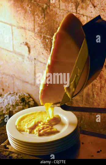 Wheel of raclette cheese melting before fireplace - Stock Image