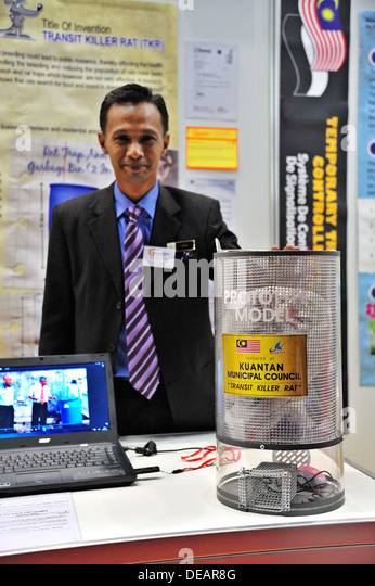 A Malaysian inventor displays his combined rubbish bin/rat trap at the 2013 Geneva Inventors' Fair. - Stock Image