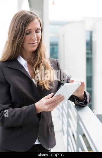 Germany, Berlin, Businesswoman using digital tablet, smiling - Stock Image