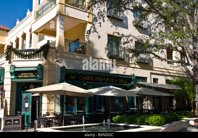 McCabes Irish Pub and Grill outside dining umbrellas exterior Old Naples Florida fl Fifth Avenue South - Stock Image