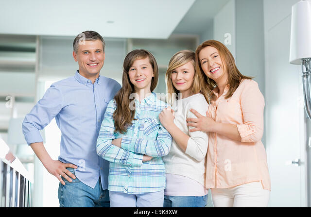 Portrait of happy family with children standing together at home - Stock Image