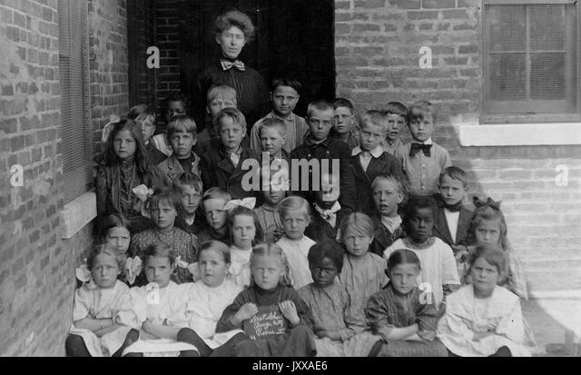 Full length landscape shot of schoolchildren, all seated with one female teacher, African American students integrated, - Stock Image