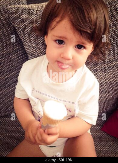Cute baby girl eating ice cream and sitting on sofa - Stock Image