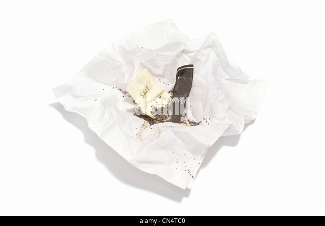 Opened sachets of salt and pepper on a paper serviette - Stock Image