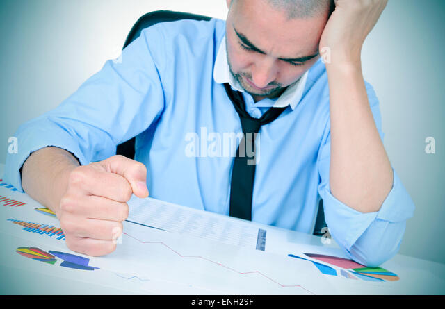 a young caucasian businessman in his office desk full of graphs and charts observing worried a chart with a downward - Stock Image