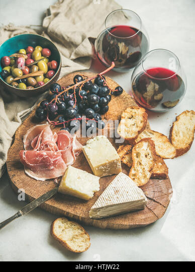 Cheese, olives, prosciutto, baguette slices, grapes and red wine - Stock Image