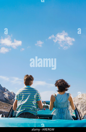 Man and woman in car looking out to sea - Stock Image