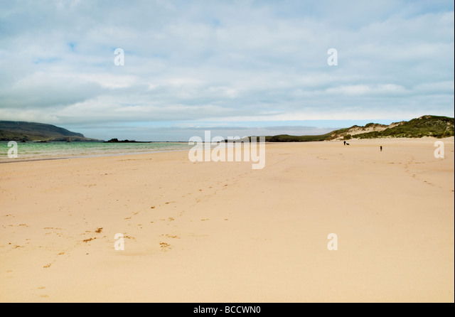 Sandy beach and bay of Balnakeil Bay, Durness, Sutherland in Scotland with man walking dogs in the distance - Stock Image