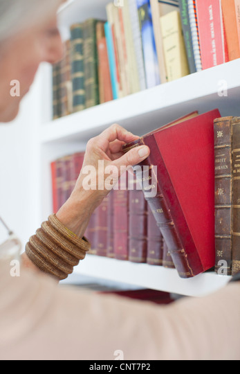 Senior woman choosing book from bookshelf - Stock Image