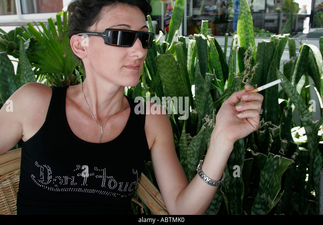 Saint Martin Marigot French Port la Royale female sunglasses cigarette - Stock Image