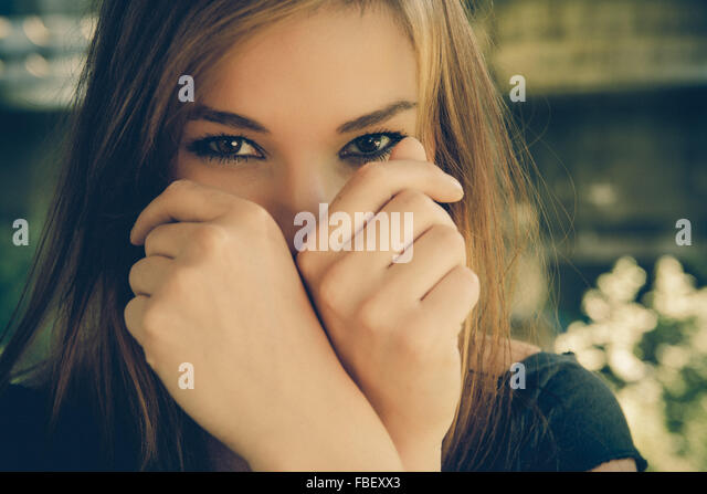 Portrait Of Young Woman Looking From Behind Fist - Stock Image