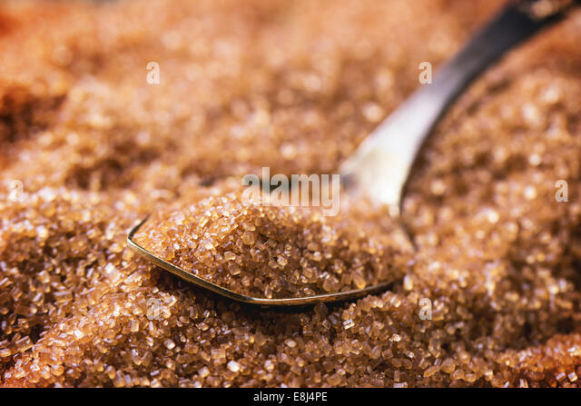 Brown sugar heap and close up of metal spoon - Stock Image