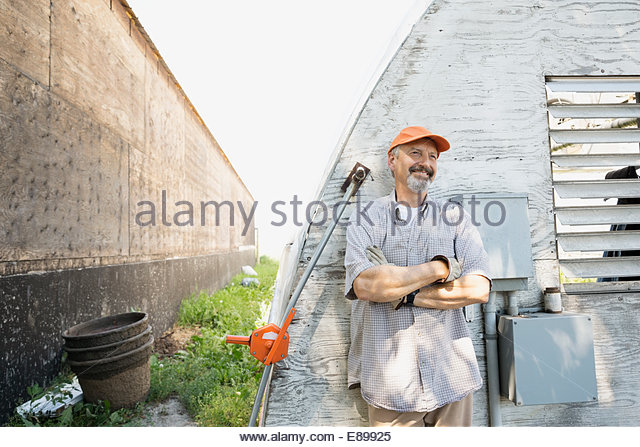 Smiling worker outside greenhouse - Stock-Bilder