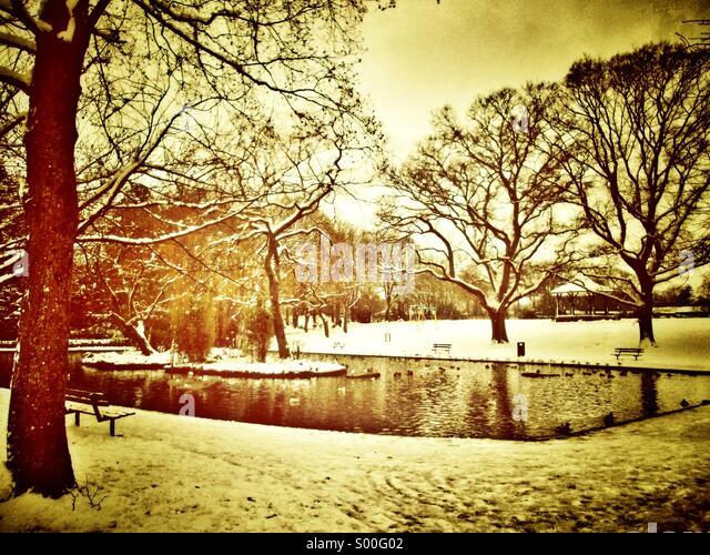 Duck pond in a park with snow in winter - Stock Image
