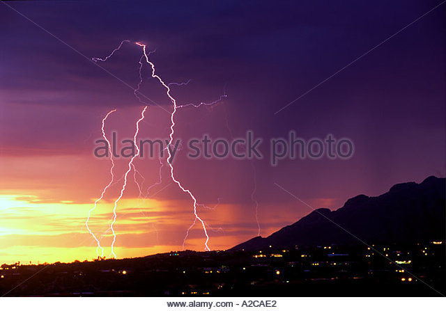 Lightning bolts crash down on Catalina Mountains from a severe thunderstorm Tucson Arizona at dusk - Stock Image